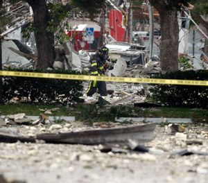 A firefighter walks through the remains of a building after an explosion. Several people were injured after a vacant pizza restaurant exploded in the South Florida shopping plaza Saturday, according to police. The restaurant was destroyed, and nearby businesses were damaged. (AP Photo/Brynn Anderson)